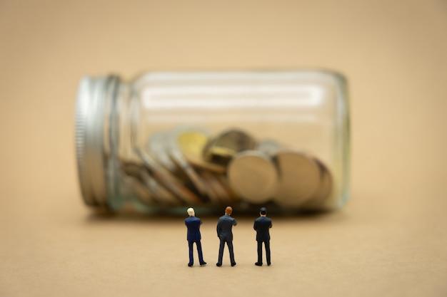 Hommes d'affaires miniatures 3 personnes debout avec dos négociation en entreprise. Photo Premium