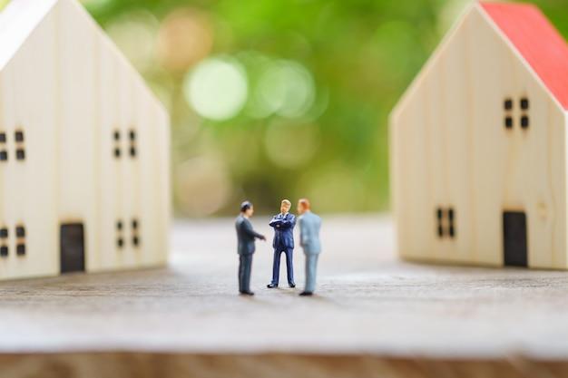 Hommes D'affaires Miniatures Debout Analyse Des Investissements Logement Ou Investissement Dans Un Bien Meuble. Photo Premium