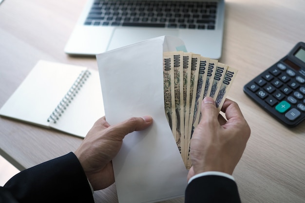 Les hommes d'affaires ouvrent une enveloppe de salaire qui est un billet de banque en yen japonais dans le bureau. Photo Premium