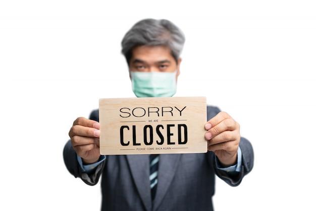 Les Hommes D'affaires Portent Des Masques Médicaux Sur Le Fond Isolé Et Tenant Désolé, Nous Sommes Signe Fermé Photo Premium