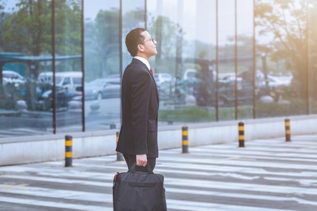Les hommes d'affaires portent des ordinateurs portables dans le parking Photo gratuit