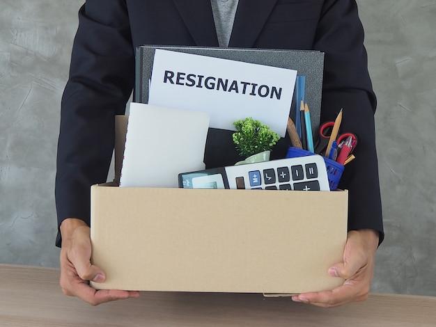 Les hommes d'affaires possèdent des affaires personnelles et des lettres de démission Photo Premium