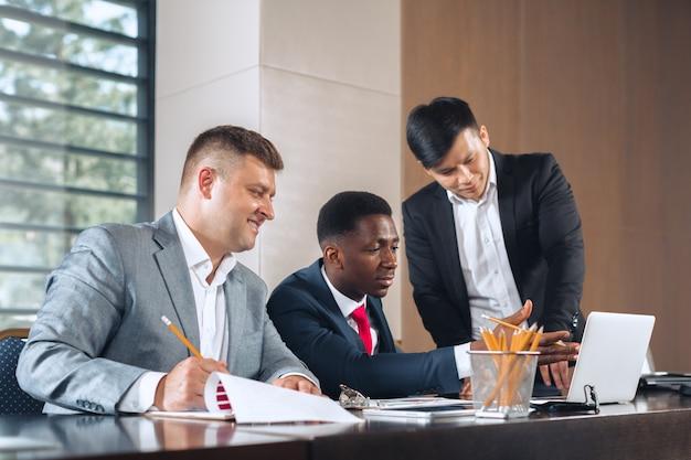 Hommes d'affaires réunis autour d'une table de réunion pour discuter de stratégie Photo Premium