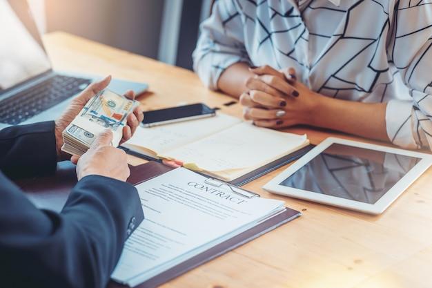 Hommes d'affaires réunis pour prendre une décision, signer un contrat et payer de l'argent. concept d'investissement Photo Premium