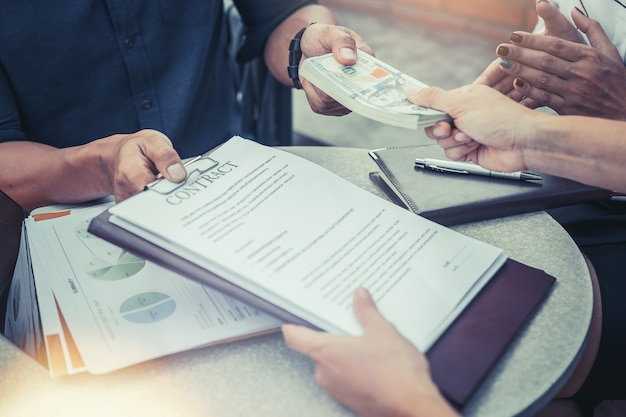 Hommes d'affaires réunis pour signer un contrat et payer de l'argent. concept d'investissement Photo Premium