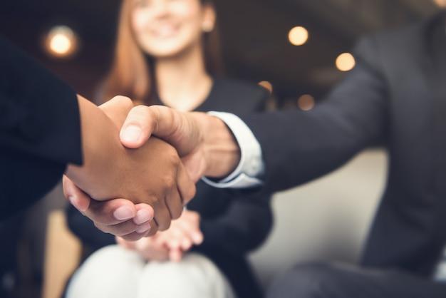 Hommes d'affaires se serrant la main après une réunion dans un café Photo Premium