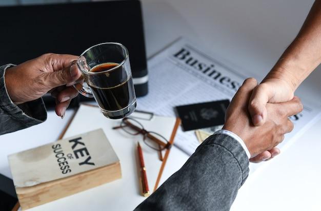 Les hommes d'affaires tenant une tasse de café sont serrer la main. Photo Premium