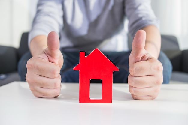 Les hommes d'affaires tiennent le modèle de maison en main Photo gratuit