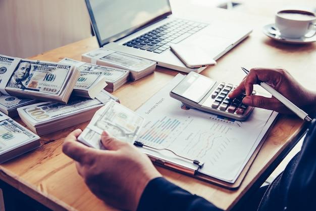 Les Hommes D'affaires Travaillent Sur Les Dollars, Calculent Les Bénéfices Et Gagnent Des Résultats, Photo Premium