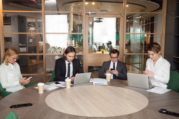 Hommes d'affaires utilisant des appareils lors d'une réunion de travail Photo gratuit