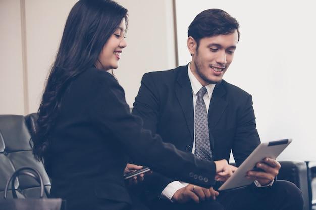Hommes d'affaires utilisant un cahier pour leurs partenaires commerciaux discutant de documents et d'idées lors d'une réunion Photo Premium