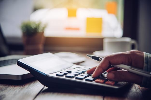 Les hommes d'affaires utilisent une calculatrice pour calculer le revenu de l'entreprise. Photo Premium