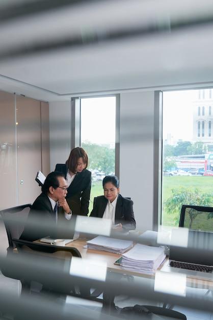 Hommes D'affaires Vietnamiens Asiatiques Discutant De Documents Lors De La Réunion Photo gratuit