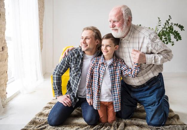 Hommes assis sur un tapis et regardant ailleurs Photo gratuit