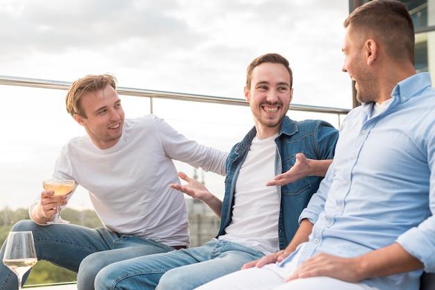 Hommes ayant une conversation lors d'une fête Photo gratuit