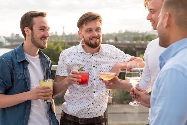 Hommes Avec Des Boissons à Une Fête Sur La Terrasse Photo gratuit