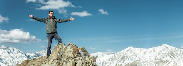 Les hommes célèbrent le succès en écartant les bras, les montagnes enneigées. réalisation de leurs objectifs Photo Premium