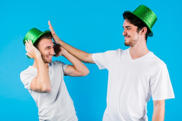 Hommes en chapeaux verts s'amusant Photo gratuit