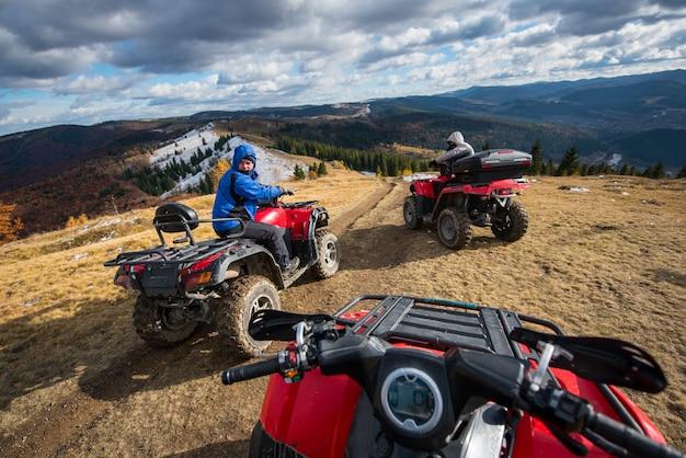 Hommes conduisant des quads devant en haut de la montagne Photo Premium