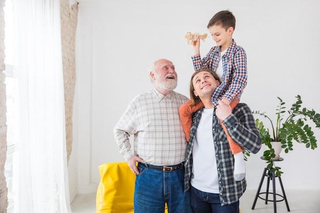 Hommes de différentes générations debout ensemble souriant tout en jouant Photo gratuit