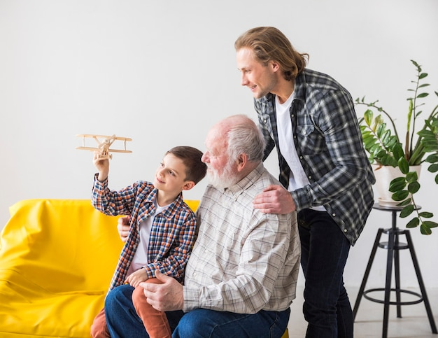 Hommes de différentes générations regardant avion jouet Photo gratuit