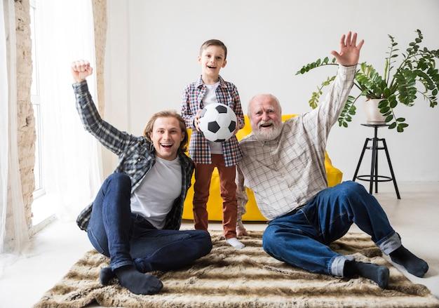 Hommes de différentes générations regardant le football Photo gratuit