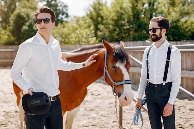 Hommes élégants, debout à côté d'un cheval dans un ranch Photo gratuit