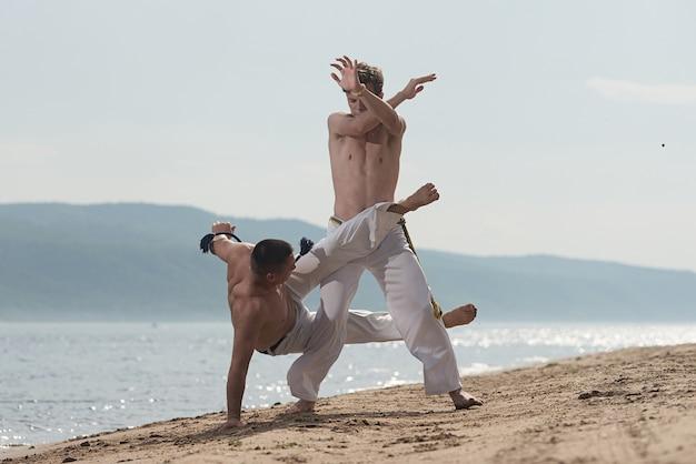 Les Hommes Entraînent La Capoeira Sur La Plage - Concept Sur Les Gens, Le Mode De Vie Et Le Sport. Photo Premium