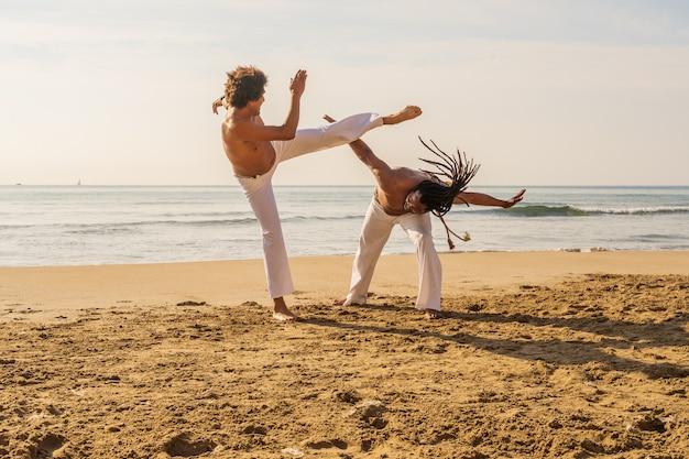 Les hommes entraînent la capoeira sur la plage - concept sur les gens, le style de vie et le sport. entraînement de deux combattants Photo Premium