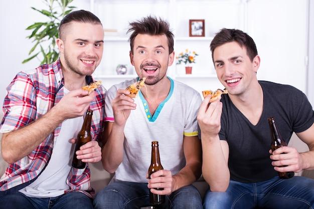 Des hommes excités regardent le football avec de la bière et des pizzas. Photo Premium