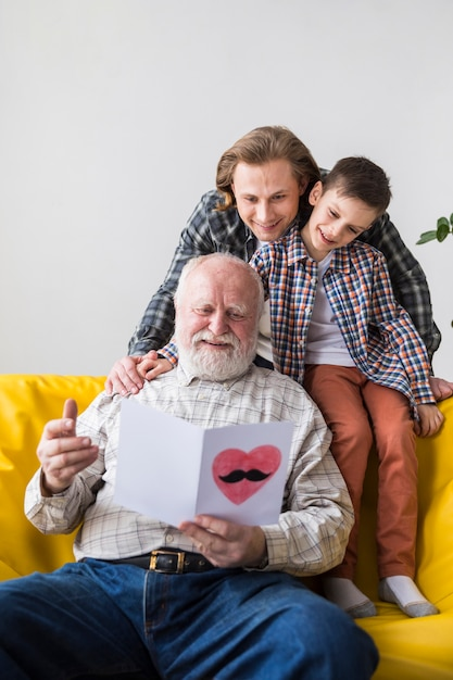 Hommes de famille de différentes générations regardant une carte-cadeau Photo gratuit