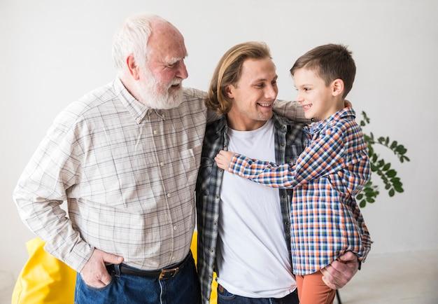 Hommes de famille de différentes générations s'embrassant Photo gratuit
