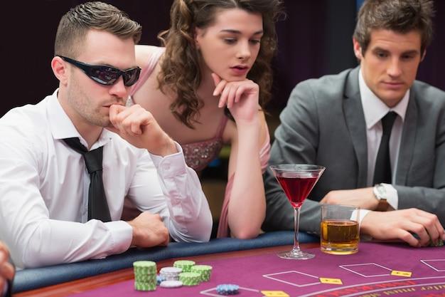 Hommes et femme assis à la table de poker Photo Premium