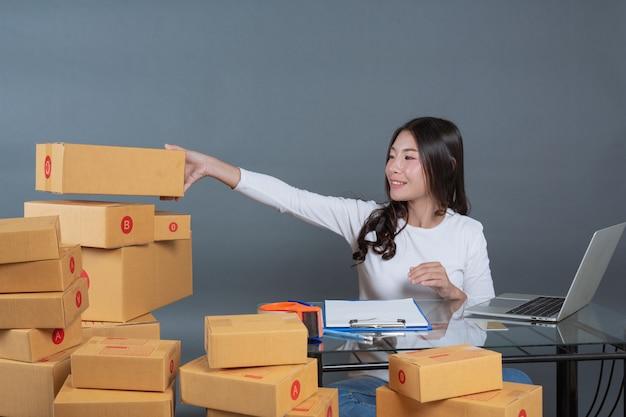 Les hommes et les femmes aident à emballer les cartons. Photo gratuit
