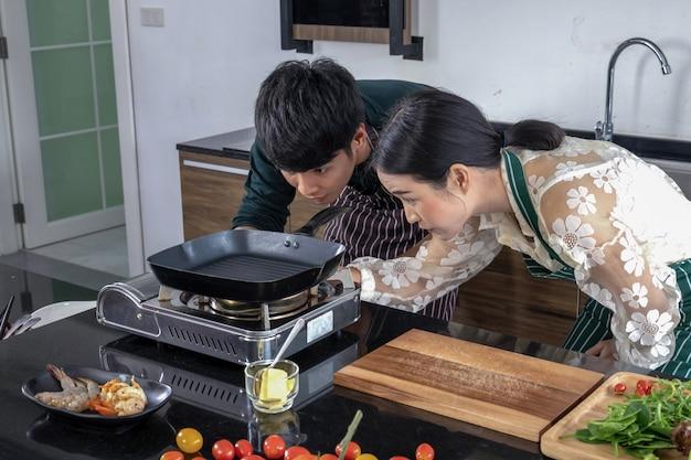 Les Hommes Et Les Femmes Aident à Ouvrir La Cuisinière à Gaz. Photo Premium
