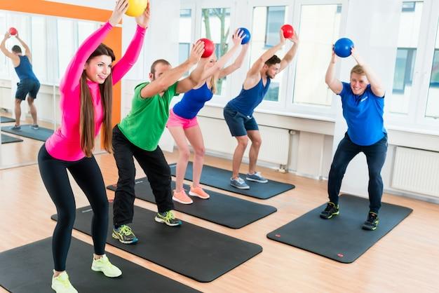 Les hommes et les femmes dans la salle de sport faisant de l'entraînement de pilates Photo Premium
