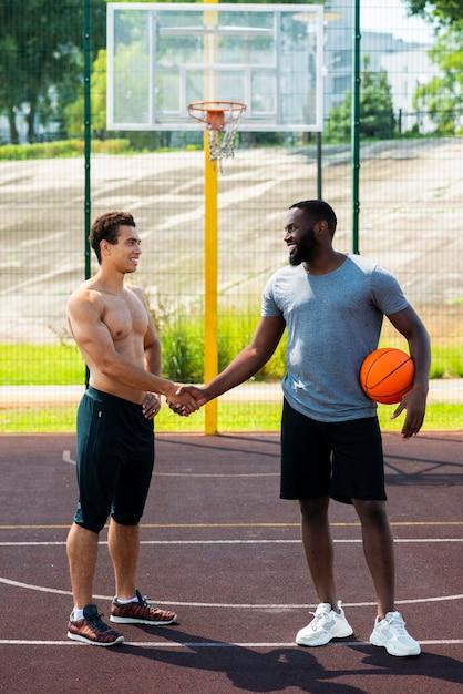 Des hommes forts se serrent la main sur le terrain de basket Photo gratuit