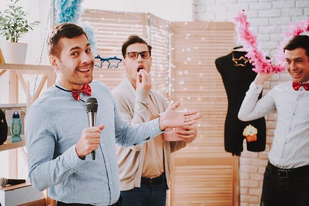 Hommes gais en vêtements colorés chantant karaoké à la fête. Photo Premium