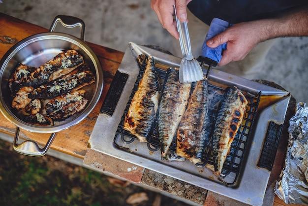 Hommes Griller Du Poisson Sur Un Barbecue électrique Photo Premium