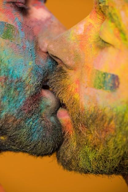 Hommes homosexuels peints artistiques s'embrassant passionnément Photo gratuit