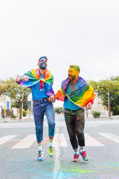 Hommes homosexuels en poudre multicolore s'amusant sur la route Photo gratuit