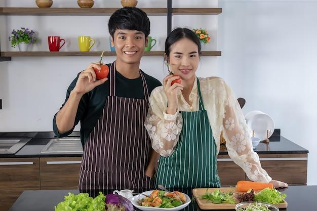 Les Hommes Et Les Jeunes Femmes Asiatiques Montrent Des Tomates Photo Premium