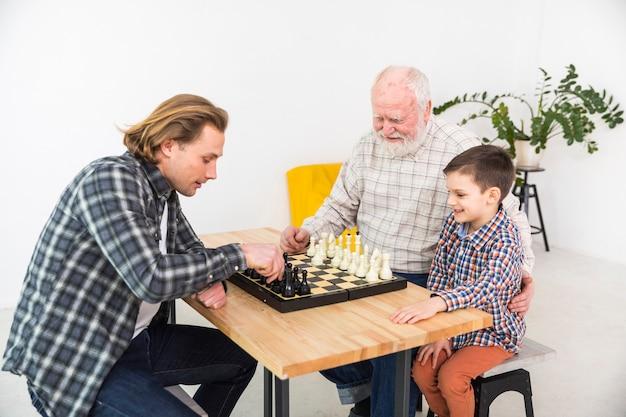 Hommes multigénérationnels jouant aux échecs Photo gratuit