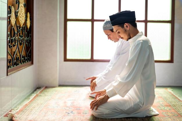 Hommes musulmans priant dans une posture de tashahhud Photo Premium