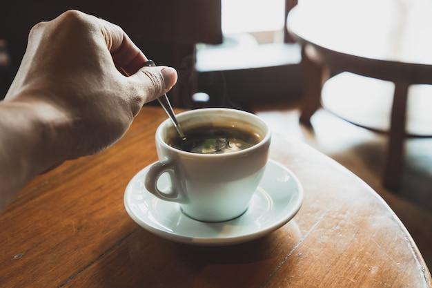 Des hommes préparent du café noir dans une tasse à café blanche posée sur une table en bois marron Photo Premium
