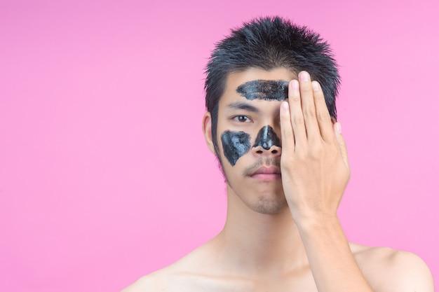 Les hommes qui utilisent leurs mains pour dissimuler la moitié de leurs visages ont des cosmétiques noirs et des roses. Photo gratuit