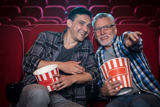 Hommes regardant un film au cinéma Photo gratuit