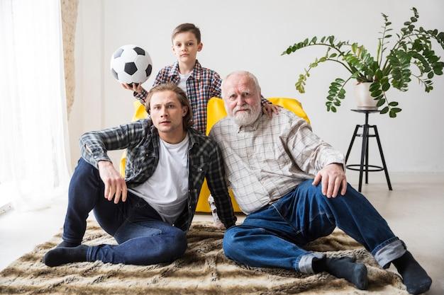 Hommes regardant le football assis sur un tapis à la maison Photo gratuit