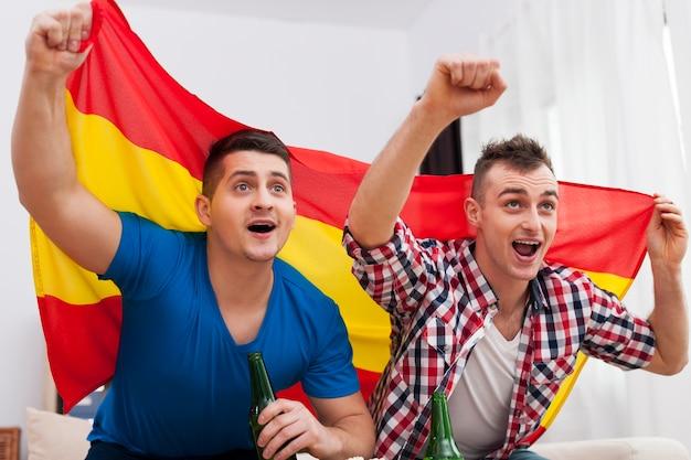 Les Hommes Regardant Un Match De Football à La Télévision Et Les Acclamations De L'équipe Espagnole Photo gratuit