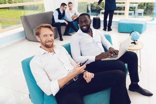 Les hommes regardent leur smartphone, l'un d'eux tient un ordinateur portable Photo Premium